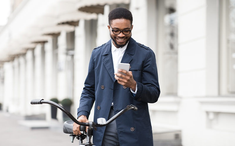 A man looking at his phone while holding his bike