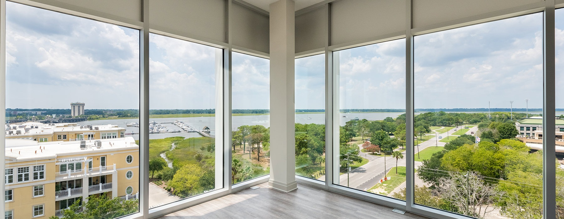 Spacious and naturally lit living room with dark plank wood flooring and a large window with a view of the bay