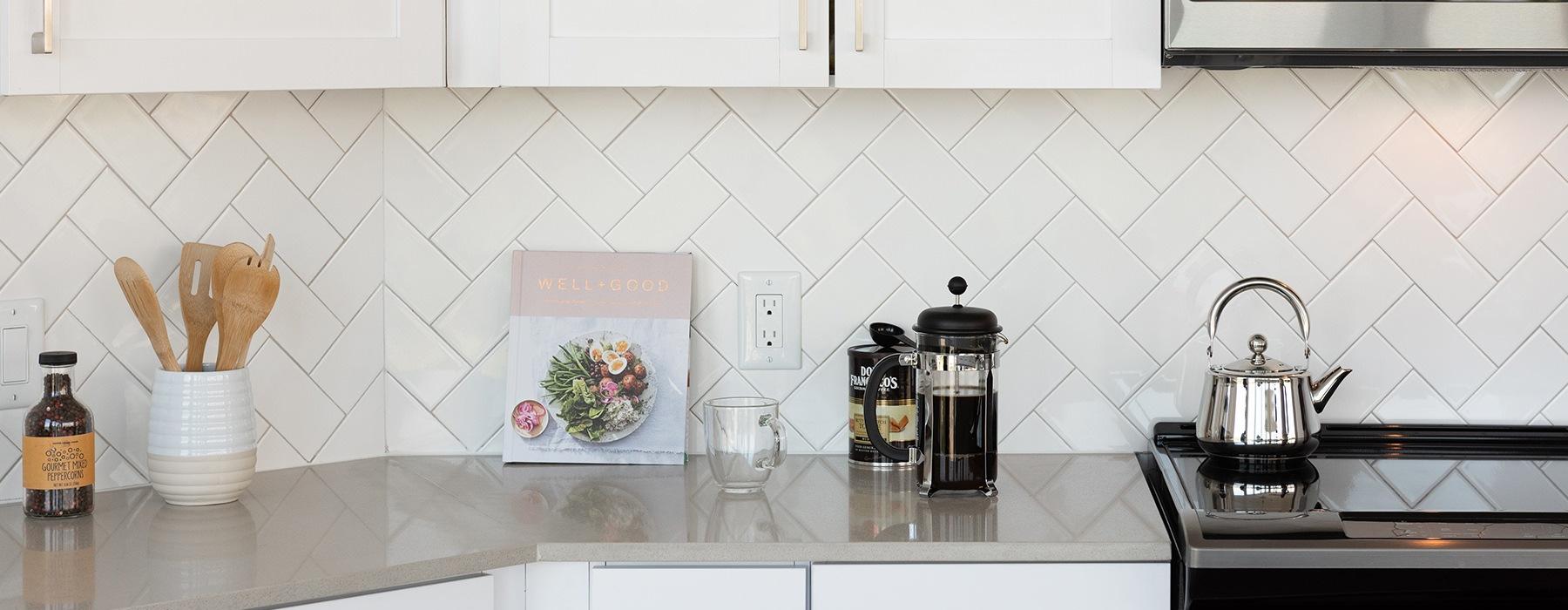 Spacious well lit kitchen with chevron style white backsplash.